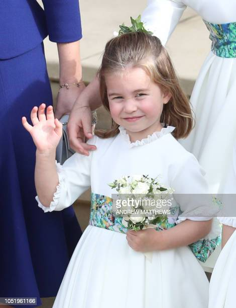 Britain's Princess Charlotte of Cambridge stands and waves on the West Steps to wave off Britain's Princess Eugenie of York and Jack Brooksbank at St...