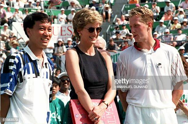 Britain's Princess Diana stands with tennis players Michael Chang of the US and Sweden's Jonas Bjorkman during the awards ceremony at the Hong Kong...