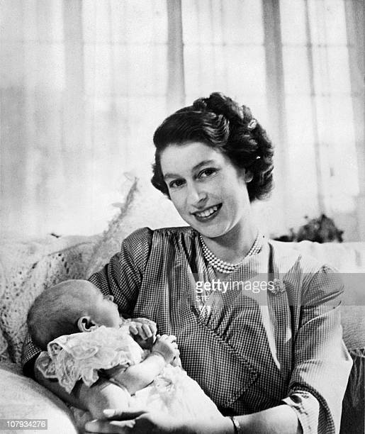 Britain's Princess Elizabeth smiles as she is holding on her lap Princess Anne born 18 August 1950