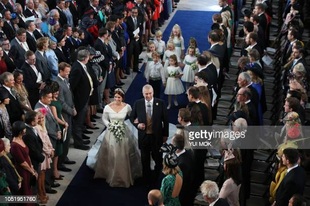 Britain's Princess Eugenie of York accompanied by Britain's Prince Andrew Duke of York walks up the aisle during her wedding ceremony to Jack...