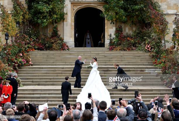 TOPSHOT Britain's Princess Eugenie of York and her father Britain's Prince Andrew Duke of York arrive at the West Door of St George's Chapel Windsor...