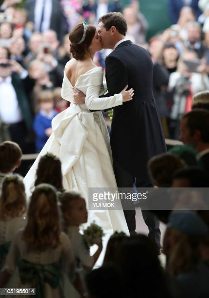 Britain's Princess Eugenie of York and her husband Jack Brooksbank kiss as they emerge from the West Door of St George's Chapel Windsor Castle in...
