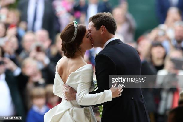 TOPSHOT Britain's Princess Eugenie of York and her husband Jack Brooksbank kiss as they emerge from the West Door of St George's Chapel Windsor...