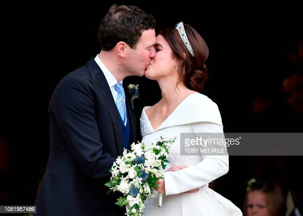 Britain's Princess Eugenie of York and her husband Jack Brooksbank kiss as they emerge from the West Door of St George's Chapel, Windsor Castle, in...