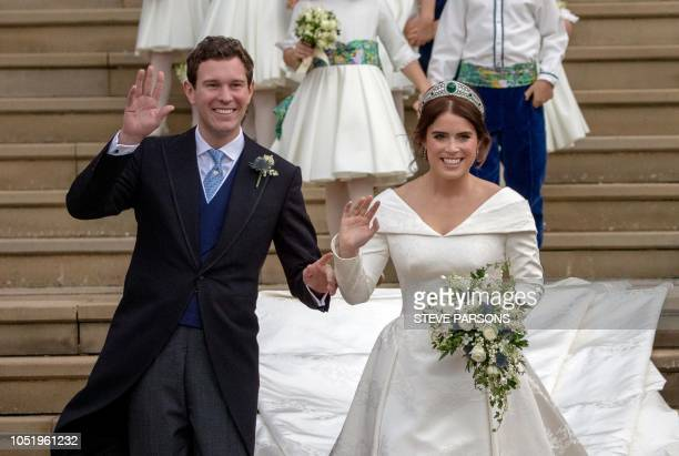 TOPSHOT Britain's Princess Eugenie of York and her husband Jack Brooksbank wave as they emerge from the West Door of St George's Chapel Windsor...