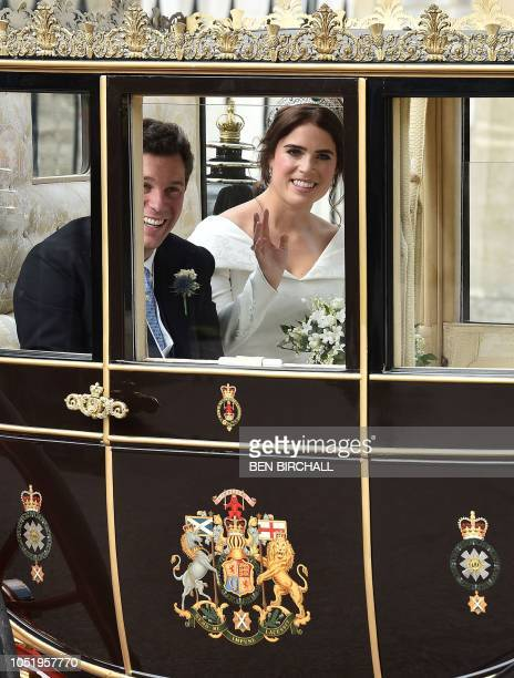 Britain's Princess Eugenie of York and her husband Jack Brooksbank travel in the Scottish State Coach at the start of their carriage procession...