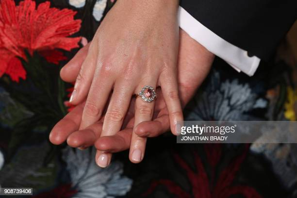 Britain's Princess Eugenie of York displays her engagement ring containing a padparadscha sapphire surrounded by diamonds as she poses with her...