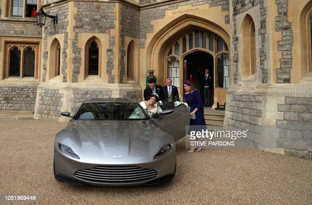 Britain's Princess Eugenie of York is helped into an Aston Martin DB10 by her sister Britain's Princess Beatrice of York as she leaves with her Jack...