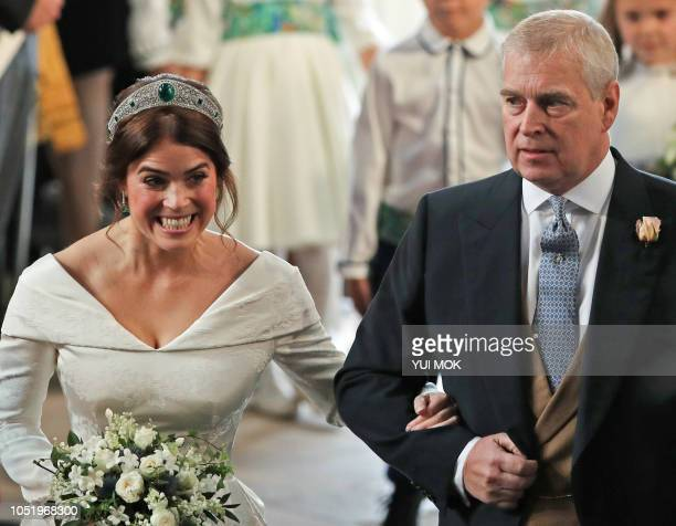 Britain's Princess Eugenie of York walks up the aisle with her father Britain's Prince Andrew, Duke of York, to marry Jack Brooksbank during their...