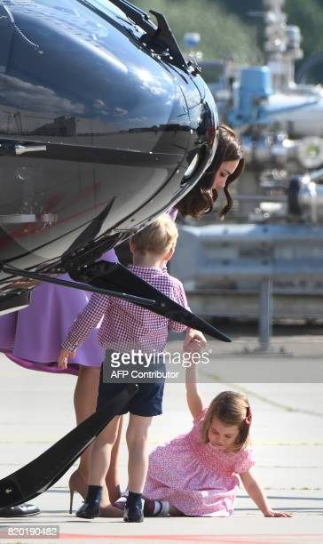 Britain's Princess Kate the Duchess of Cambridge attends to her children Prince George and Princess Charlotte as they visit an Airbus helicopter on...