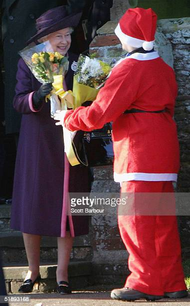Britain's Queen Elizabeth II accepts a bunch of flower from a boy dresses as Father Christmas after she attended the Christmas Day service at...