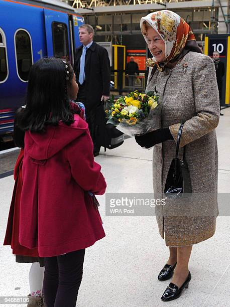 Britain's Queen Elizabeth II accepts a posy of flowers from a young girl before she boards a First Capital Connect train at King's Cross Station on...