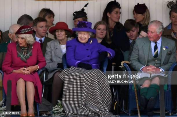 Britain's Queen Elizabeth II accompanied by Britain's Camilla Duchess of Cornwall and Britain's Prince Charles Prince of Wales looks on during the...