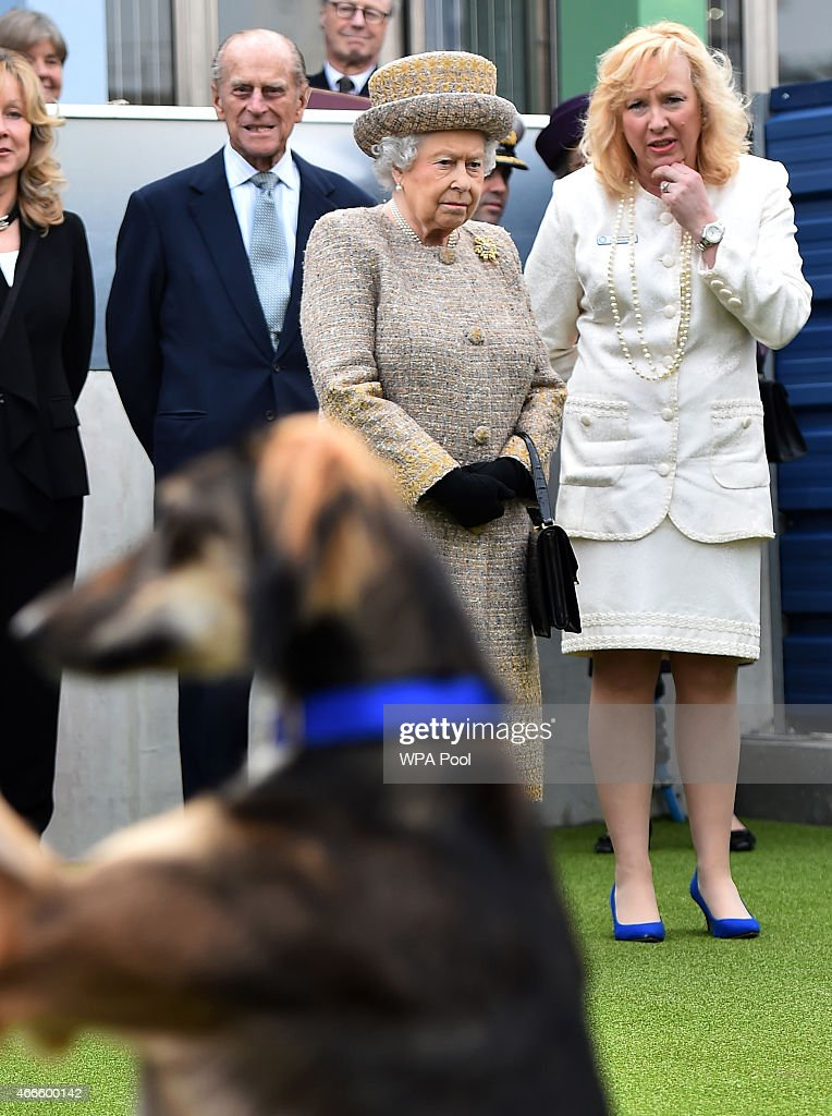 Britain's Queen Elizabeth II accompanied by Britain's Prince Philip, Duke of Edinburgh speak with Chief Executive Officer Claire Horton as they attend the opening of the new Mary Tealby dog kennels at Battersea Dogs and Cats Home in London on March 17, 2015.