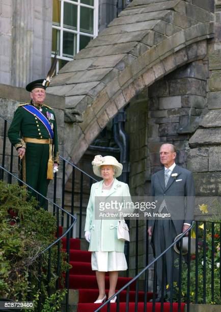 Britain's Queen Elizabeth II accompanied by The Duke of Edinburgh stand as the National Anthum is played upon their arrival for the Garden Party at...