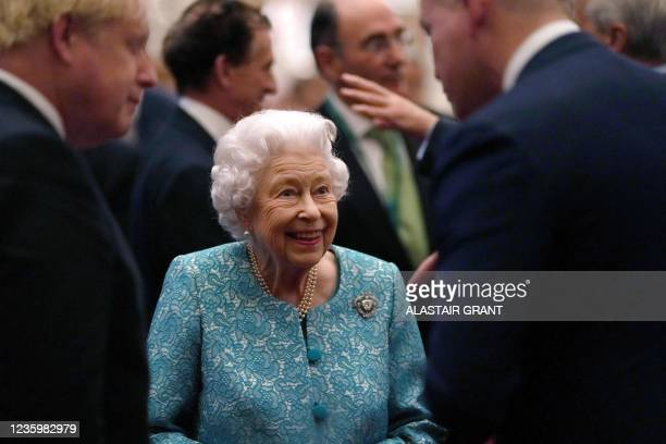 Britain's Queen Elizabeth II and Britain's Prime Minister Boris Johnson greet guests during a reception to mark the Global Investment Summit, at...