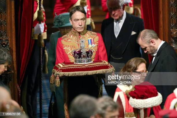 Britain's Queen Elizabeth II and Britain's Prince Charles Prince of Wales walk behind the Imperial State Crown as they arrive in the House of Lords...