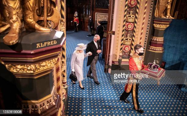 Britain's Queen Elizabeth II and Britain's Prince Charles, Prince of Wales walk behind the Imperial State Crown as they process through the Royal...