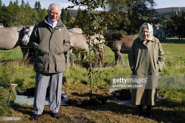 Britain's Queen Elizabeth II and Britain's Prince Charles, Prince of Wales pose alongside the tree which they planted to mark the start of the...