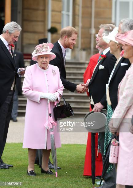 Britain's Queen Elizabeth II and Britain's Prince Harry Duke of Sussex greet guests at the Queen's Garden Party in Buckingham Palace central London...