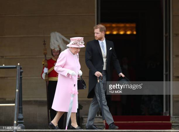 Britain's Queen Elizabeth II and Britain's Prince Harry, Duke of Sussex arrive at the Queen's Garden Party in Buckingham Palace, central London on...