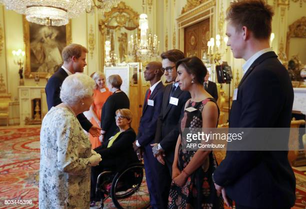 Britain's Queen Elizabeth II and Britain's Prince Harry greet Dame Tanni GreyThompson Mo Farah Liam Payne Anita Rani and Caspar Lee during a...