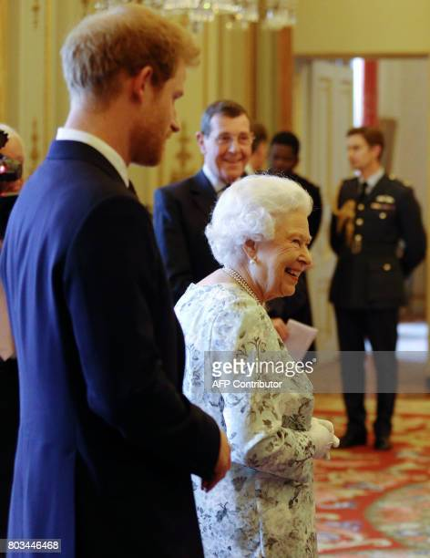 Britain's Queen Elizabeth II and Britain's Prince Harry greet guests during a reception prior to the Queen's Young Leaders Awards ceremony at...