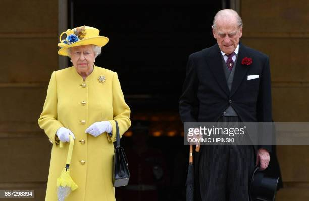 Britain's Queen Elizabeth II and Britain's Prince Philip Duke of Edinburgh observe a minute's silence at the start of a Special Garden Party at...