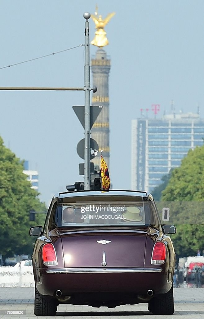 Britain's Queen Elizabeth II and Britain's Prince Philip, Duke of Edinburgh drive through Berlin's landmark Brandenburg Gate in a car on June 26, 2015, as they leave Berlin. British Queen Elizabeth II ends her three-day visit to Germany.