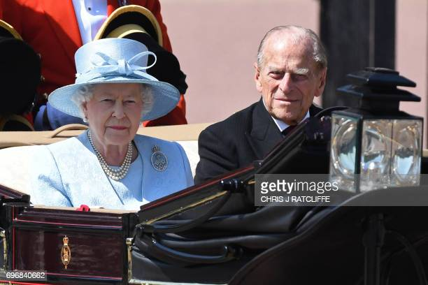 TOPSHOT Britain's Queen Elizabeth II and Britain's Prince Philip Duke of Edinburgh travel in a horsedrawn carriage past Buckingham Palace on their...