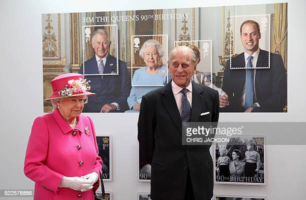 Britain's Queen Elizabeth II and Britain's Prince Philip Duke of Edinburgh pass a giant photograph taken to be used as part of a series of 10 Royal...