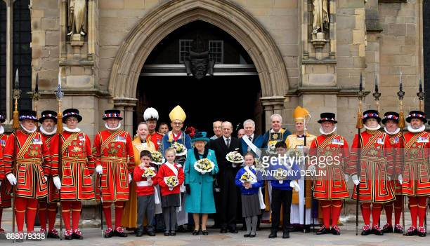 Britain's Queen Elizabeth II and Britain's Prince Philip Duke of Edinburgh pose with Yeoman of the Guard following the Royal Maundy service at...