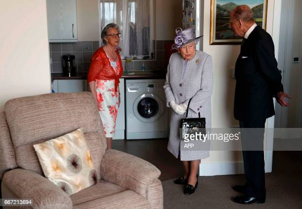 Britain's Queen Elizabeth II and Britain's Prince Philip Duke of Edinburgh talk with resident Pauline Stainsby as they view her home during their...