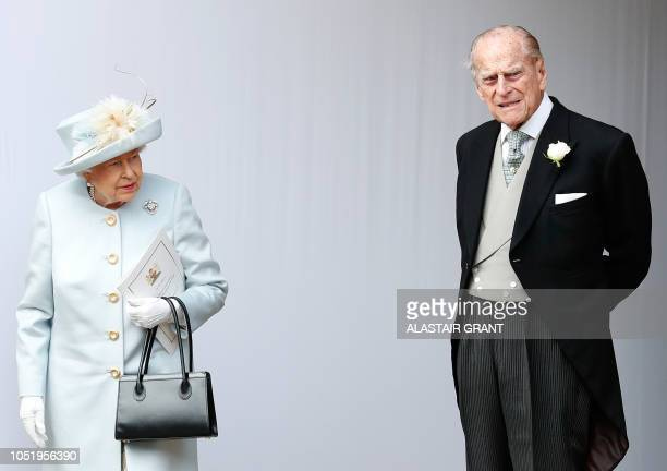 TOPSHOT Britain's Queen Elizabeth II and Britain's Prince Philip Duke of Edinburgh wait for the carriage carrying Princess Eugenie of York and her...