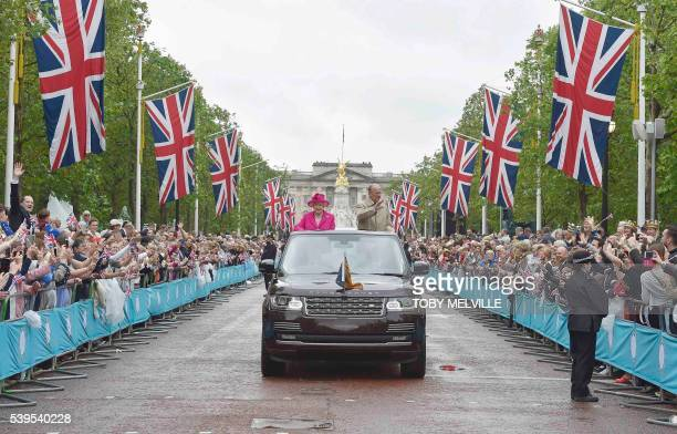 Britain's Queen Elizabeth II and Britain's Prince Philip Duke of Edinburgh wave to guests attending the Patron's Lunch on the Mall an event to mark...