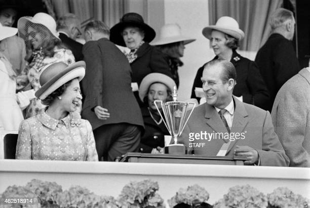 Britain's Queen Elizabeth II and her husband Prince Philip Duke of Edinburgh share a laugh in May 1972 as they attend a horse race at Longchamp...