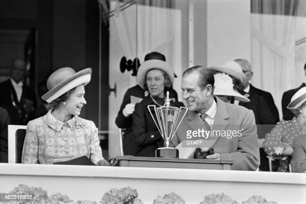 Britain's Queen Elizabeth II and her husband Prince Philip Duke of Edinburgh share a smile in May 1972 as they attend a horse race at Longchamp...