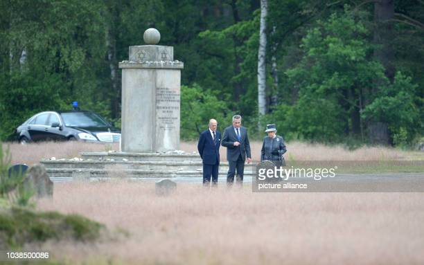 Britain's Queen Elizabeth II and her husband Prince Philip listen to explanations of JensChristian Wagner director of the memorial center at the site...