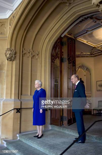 Britain's Queen Elizabeth II and her husband Prince Philip stand in front of the entrance of Windsor Castle in south-east England after biding...