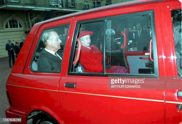 Britain's Queen Elizabeth II and her husband the Duke of Edinburgh take a ride in a specially converted gas-powered London taxi 07 May to promote the...