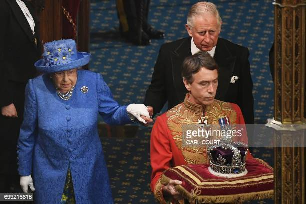 Britain's Queen Elizabeth II and her son Britain's Prince Charles Prince of Wales follow the Imperial State Crown in to the House of Lords during the...