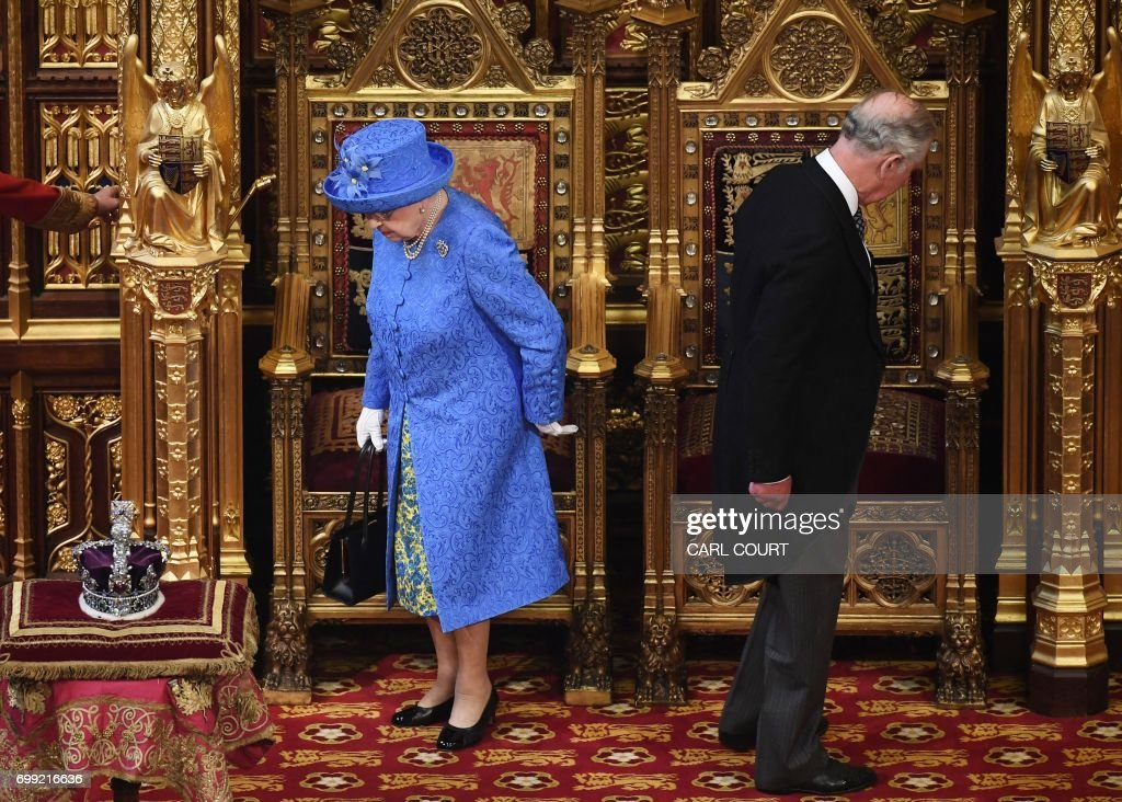 Britain's Queen Elizabeth II and her son Britain's Prince Charles, Prince of Wales prepare to take their seats as they arrive in the House of Lords during the State Opening of Parliament in the Houses of Parliament in London on June 21, 2017. Queen Elizabeth II will formally open parliament and announce the British government's legislative programme on Wednesday, two days later than planned. The state opening, a ceremony full of pomp in which the monarch reads out the Queen's Speech detailing the government's programme for the coming year, was due to take place on June 19, but was delayed after Britain's Prime Minister Theresa May's Conservative party lost their majority in the House of Commons in the June 8 election. / AFP PHOTO / POOL / Carl Court