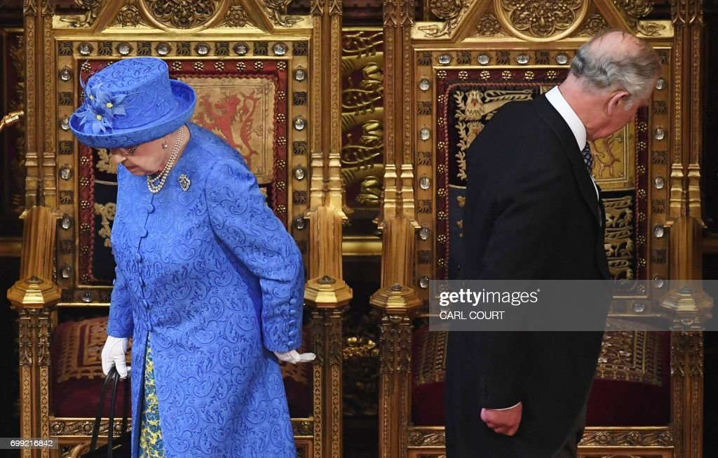 TOPSHOT - Britain's Queen Elizabeth II and her son Britain's Prince Charles, Prince of Wales prepare to take their seats as they arrive in the House of Lords during the State Opening of Parliament in the Houses of Parliament in London on June 21, 2017. Queen Elizabeth II will formally open parliament and announce the British government's legislative programme on Wednesday, two days later than planned. The state opening, a ceremony full of pomp in which the monarch reads out the Queen's Speech detailing the government's programme for the coming year, was due to take place on June 19, but was delayed after Britain's Prime Minister Theresa May's Conservative party lost their majority in the House of Commons in the June 8 election. / AFP PHOTO / POOL / Carl Court