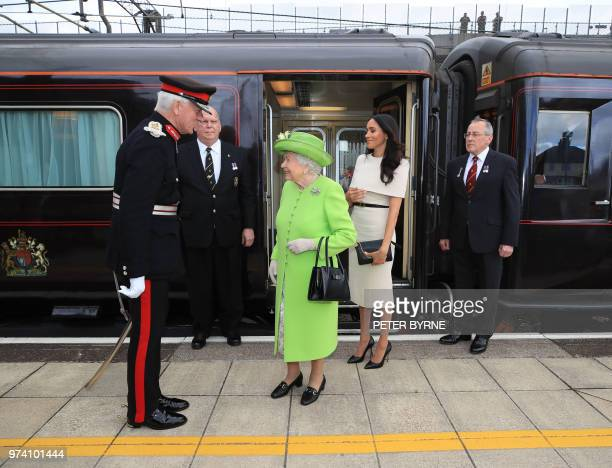 Britain's Queen Elizabeth II and Meghan Duchess of Sussex arrive by royal train at Runcorn Station in Runcorn to carry out engagements in Cheshire on...
