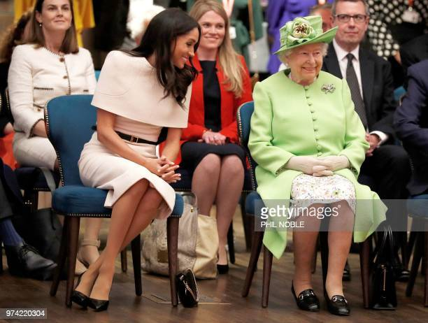 TOPSHOT Britain's Queen Elizabeth II and Meghan Duchess of Sussex gesture during their visit to the Storyhouse in Chester Cheshire on June 14 2018