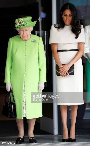 Britain's Queen Elizabeth II and Meghan Duchess of Sussex observe a moment of silence in memory of the victims of the Grenfell Tower fire during...