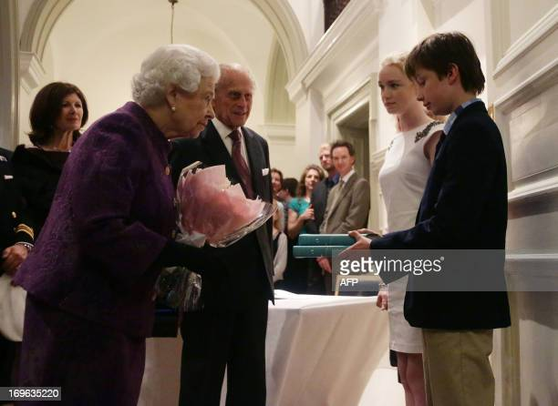 Britain's Queen Elizabeth II and Prince Philip Duke of Edinburgh are presented with copies of books by relatives of members of the 1953 Everest...