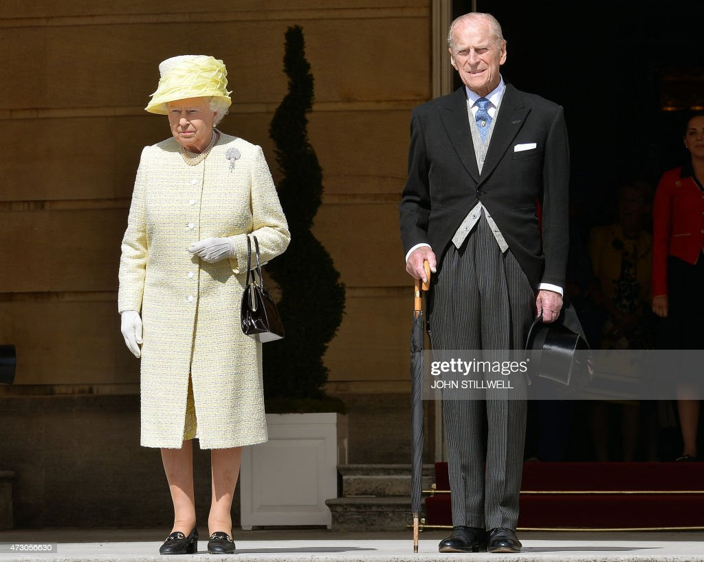 Britain's Queen Elizabeth II (L) and Prince Philip, Duke of Edinburgh stand for the national anthem at a garden party held at Buckingham Palace, central London on May 12, 2015. AFP PHOTO / POOL /John Stillwell