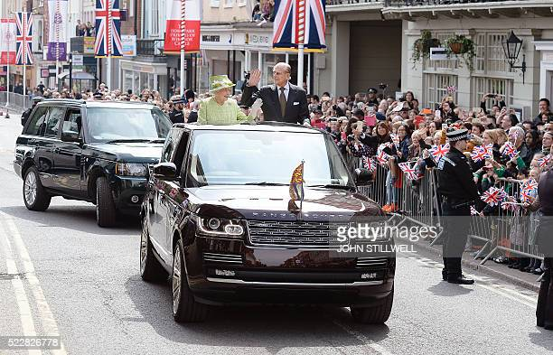 Britain's Queen Elizabeth II and Prince Philip Duke of Edinburgh wave to wellwishers during a 'walkabout' on her 90th birthday in Windsor west of...