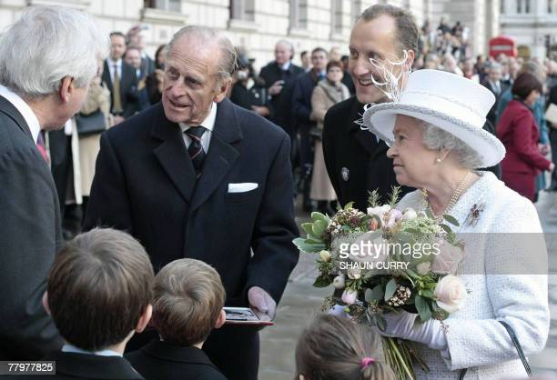 Britain's Queen Elizabeth II and Prince Philip talk with members of the public as they unveil the Jubilee Walkway panel on Parliament Square in...